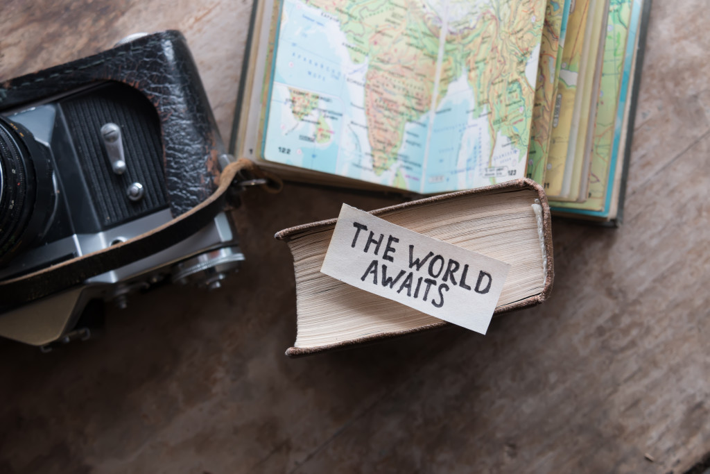 text The World Awaits, travel concept